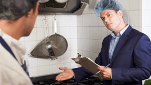 Surveyor explains findings to kitchen staff